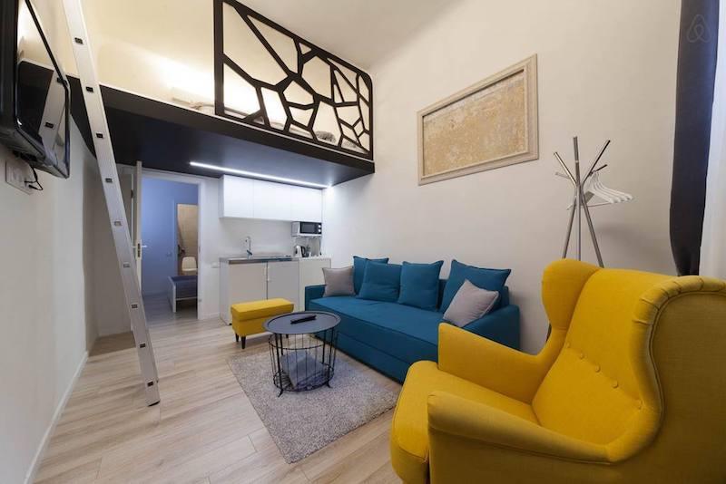 Заходишь и попадаешь в небольшую уютную кухню-гостиную. Над кухонным уголком - второй этаж с полутораспальной кроватью (до потолка там чуть больше метра, вполне комфортно). Фотка с АирБНБ: